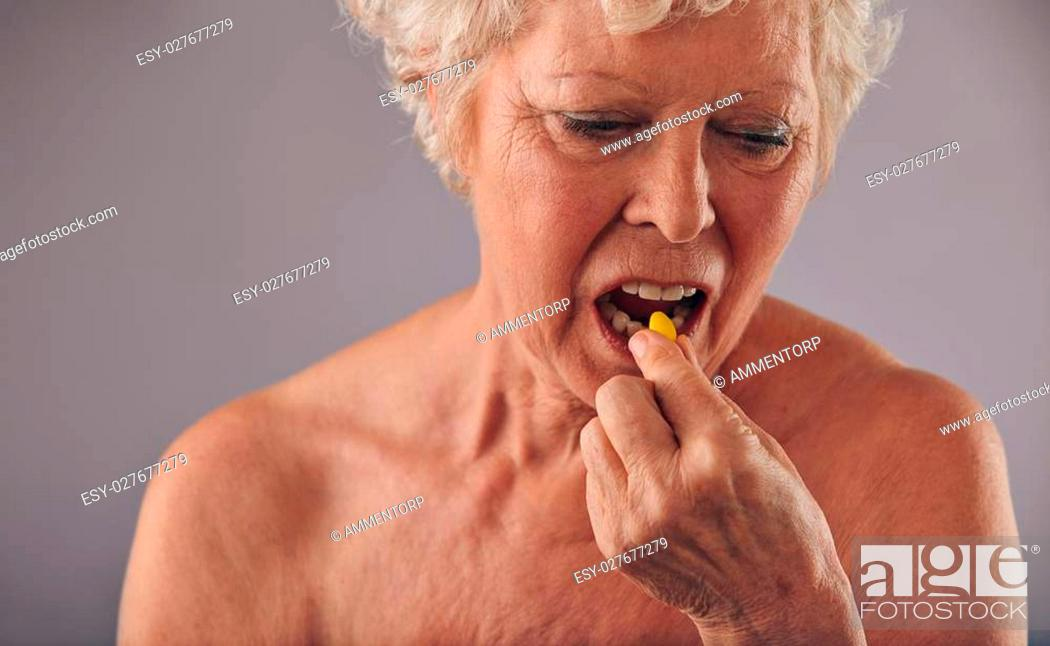 Stock Photo: Portrait of senior caucasian woman having a pill against grey background. Naked woman talking medicine.