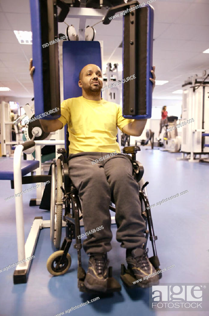 Stock Photo: Disabled man using gym equipment.