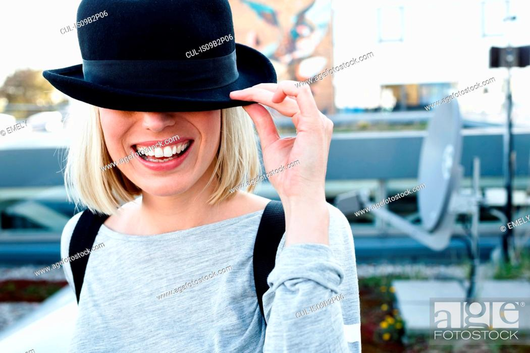 Stock Photo: Portrait of blonde haired woman wearing hat over eyes smiling.