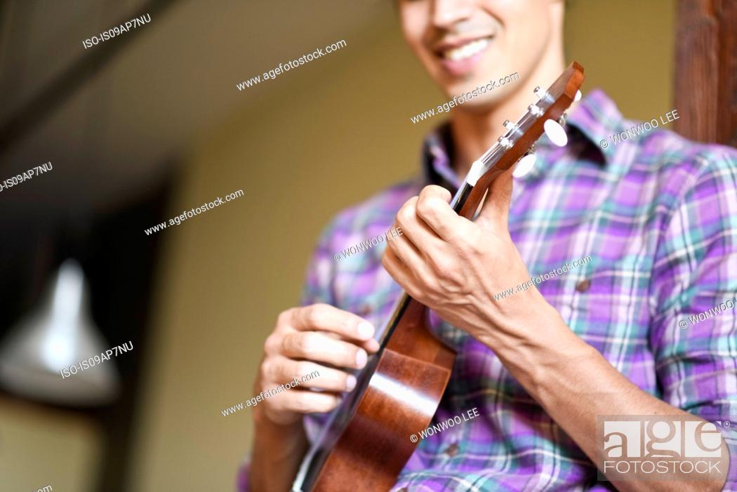 Imagen: Young man playing ukulele.