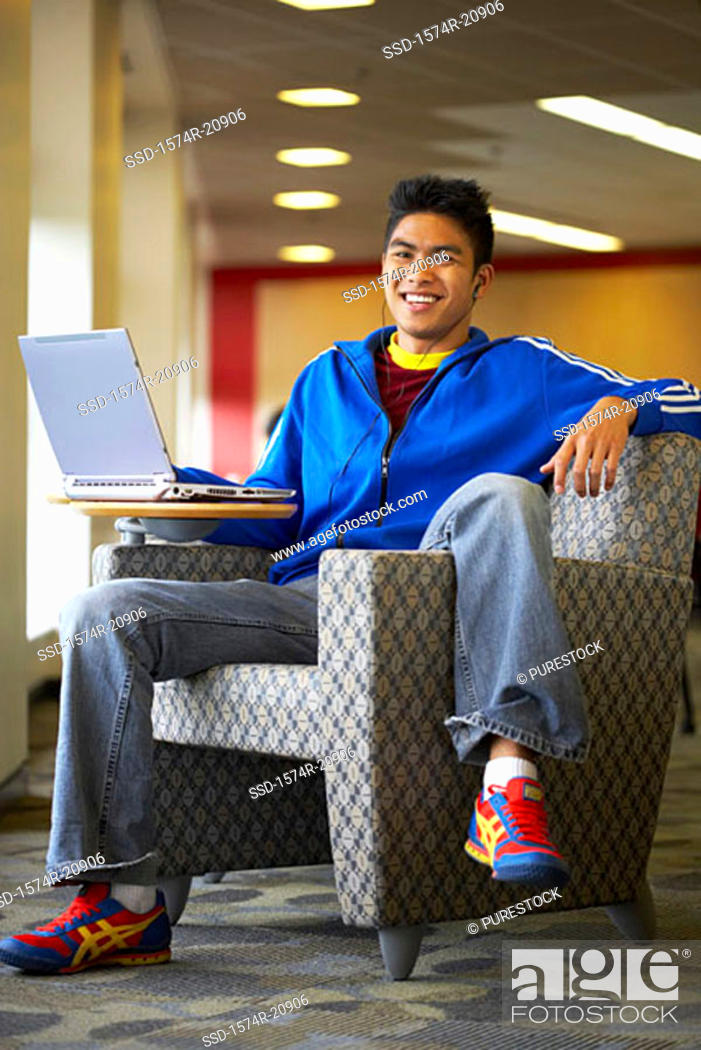 Stock Photo: Portrait of a college student sitting in an armchair with a laptop.