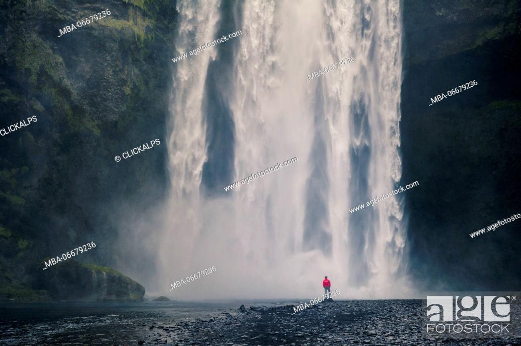 Stock Photo: Southern Iceland. Man stands below the Skogafoss waterfall.