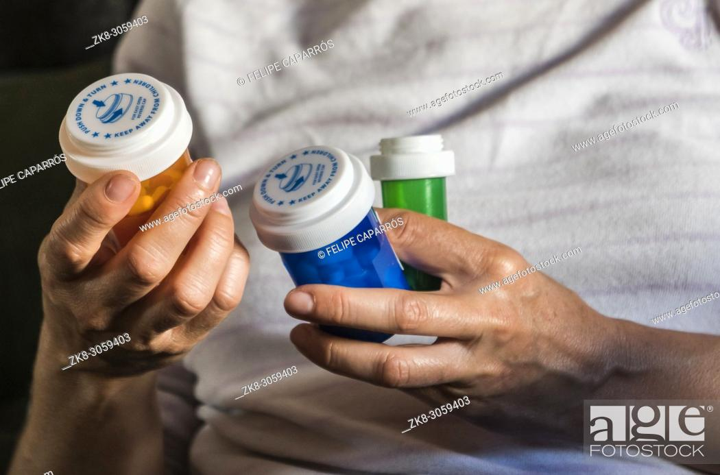 Stock Photo: Woman examining medication treatment, several bottles in the hand, conceptual image.