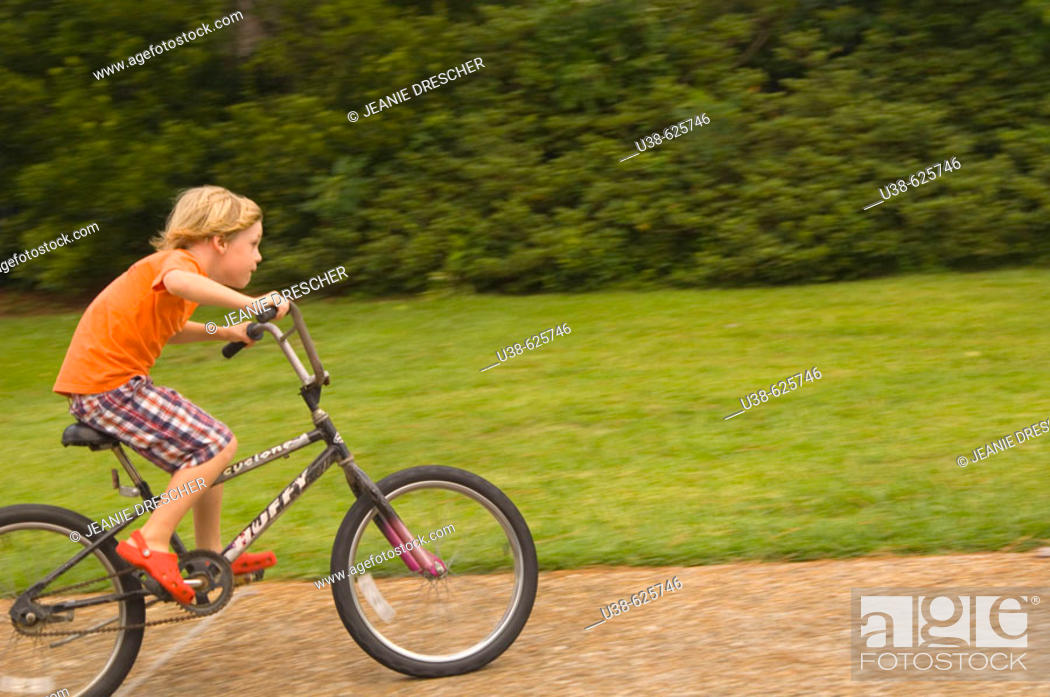 Stock Photo: 6 year old boy riding a bike very fast. Point Harbor, North Carolina. USA.