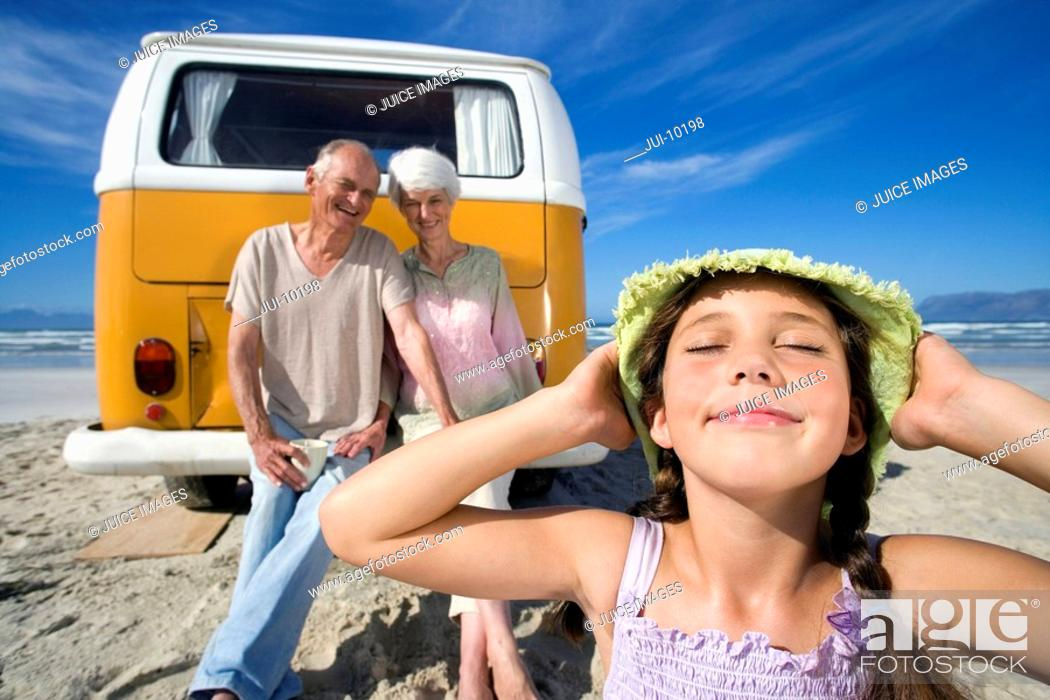 Stock Photo: Girl 7-9 holding hat on head on beach by grandparents on back of camper van, smiling, close-up.