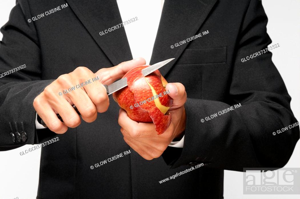 Stock Photo: Mid section view of a waiter peeling an apple.