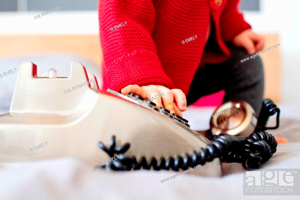 Stock Photo: Cropped shot of baby girl dialling landline telephone.