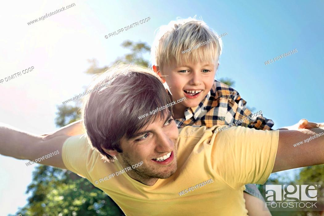 Stock Photo: Germany, Cologne, Father and son flying, smiling.