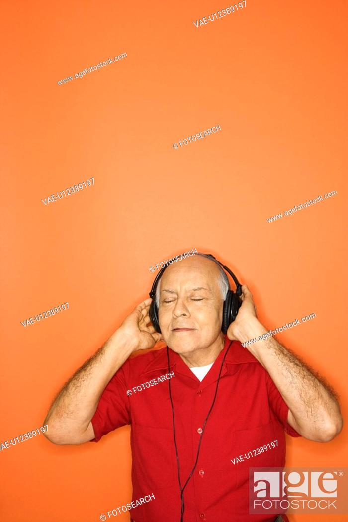 Stock Photo: Mature adult Caucasian male listening to headphones.,.