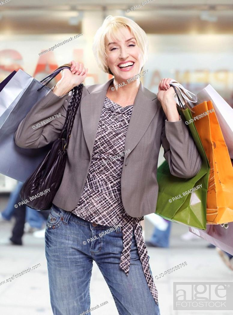 Stock Photo: Woman in mall with shopping bags.