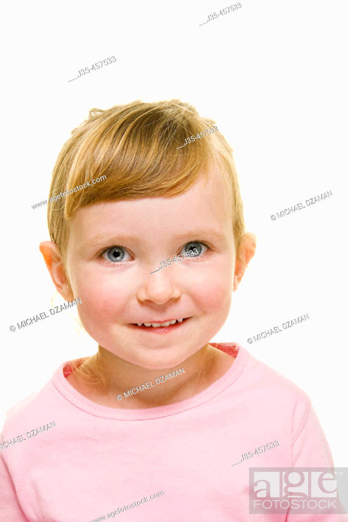 Stock Photo: A three year old girl with blonde hair wearing  a pink top and hair pulled back,  looks into camera with a happy expression.