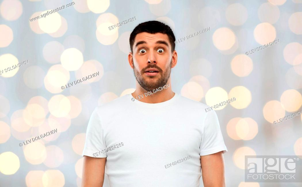 Stock Photo: emotion, advertisement and people concept - scared man in white t-shirt over holidays lights background.