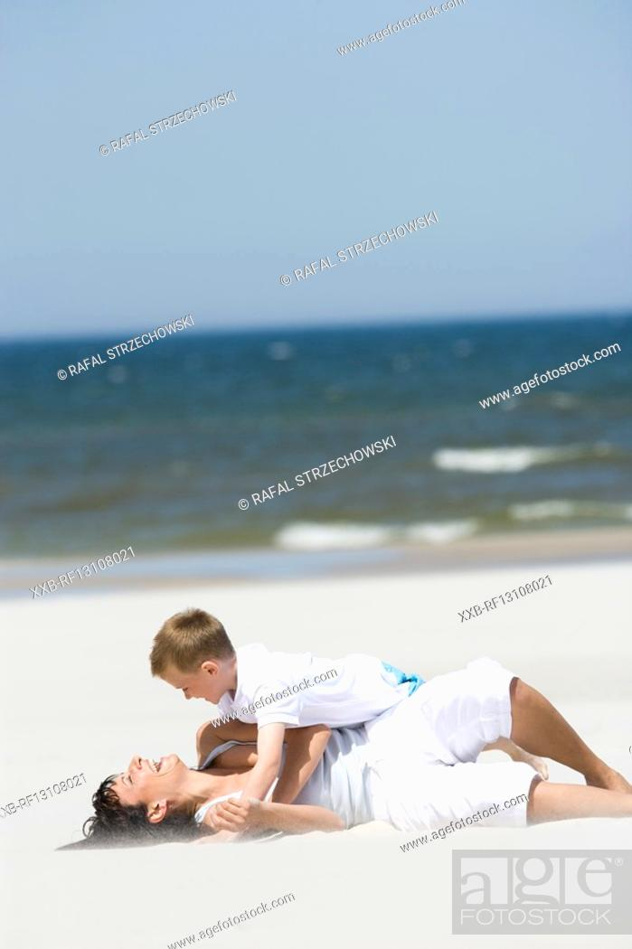 Stock Photo: mother playing with son on beach.