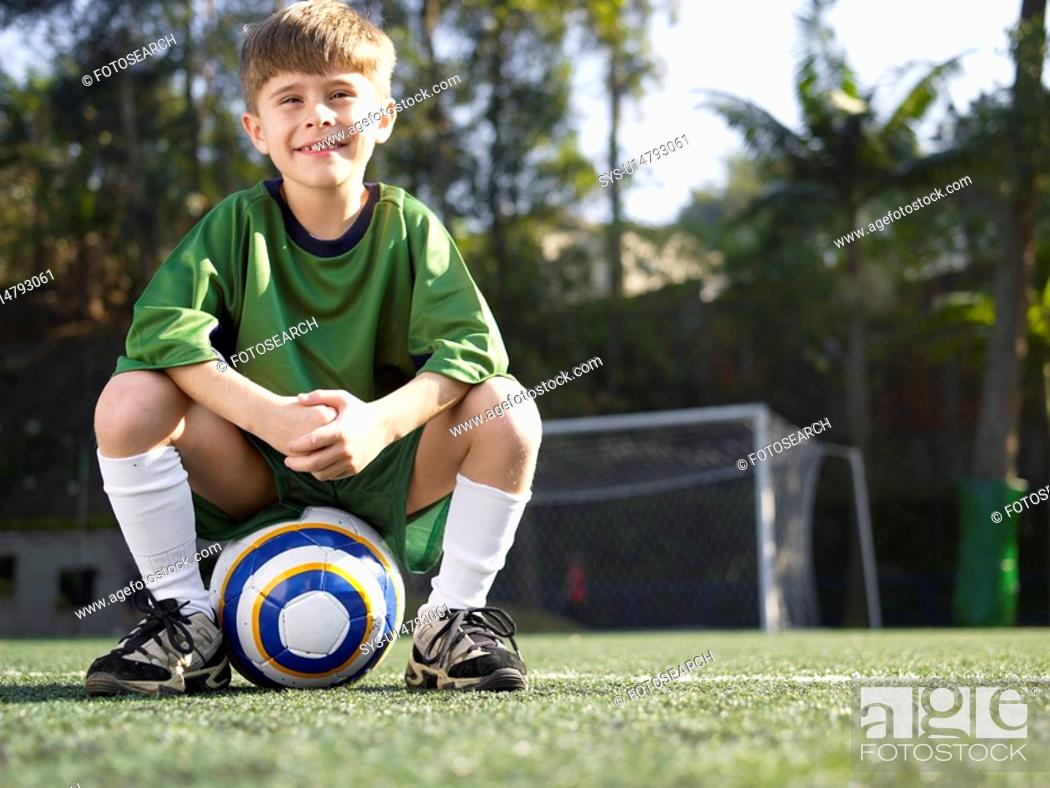Stock Photo: Boy sitting on soccer ball portrait, low angle view.