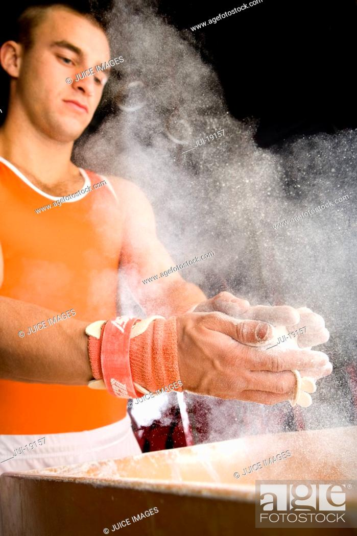 Stock Photo: Male gymnast coating hands in powder, low angle view.