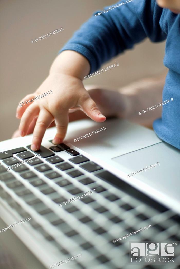 Stock Photo: Child's hand touching laptop keyboard.