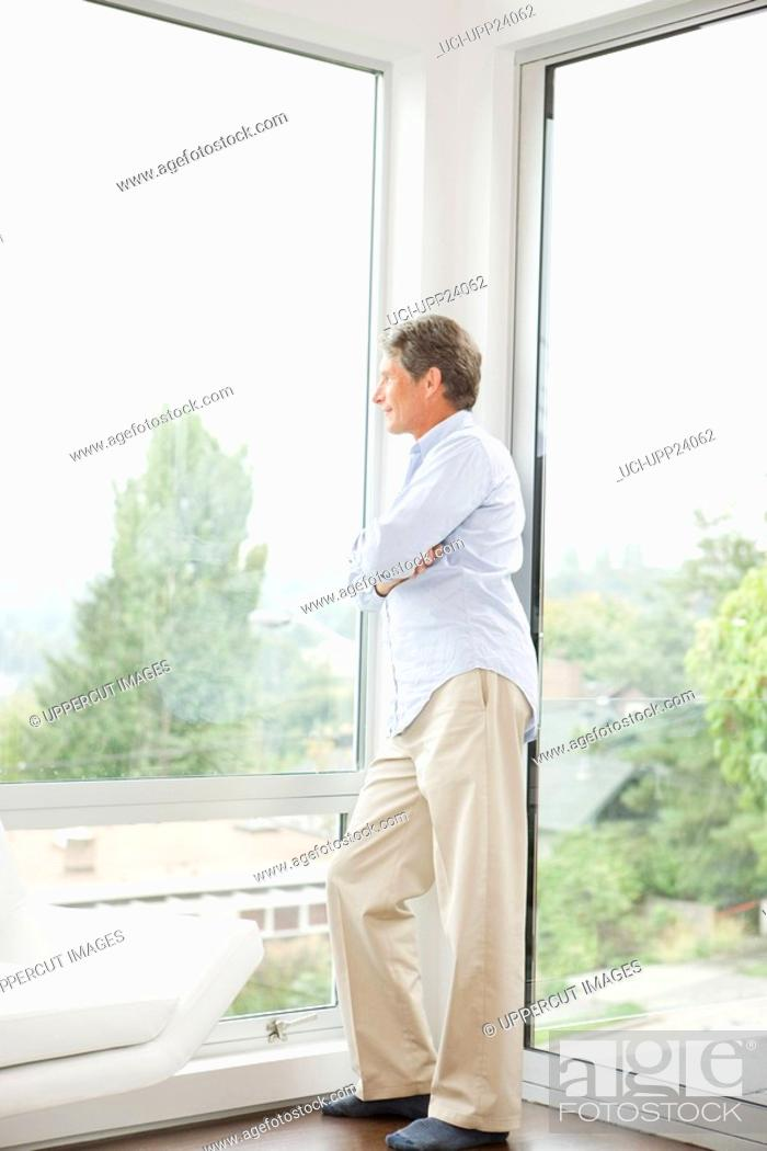 Stock Photo: Man leaning against living room window.