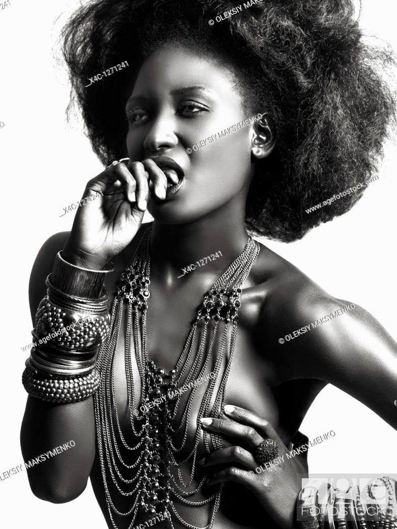 Stock Photo: High fashion photo of a young beautiful woman with shiny black skin wearing jewelry.