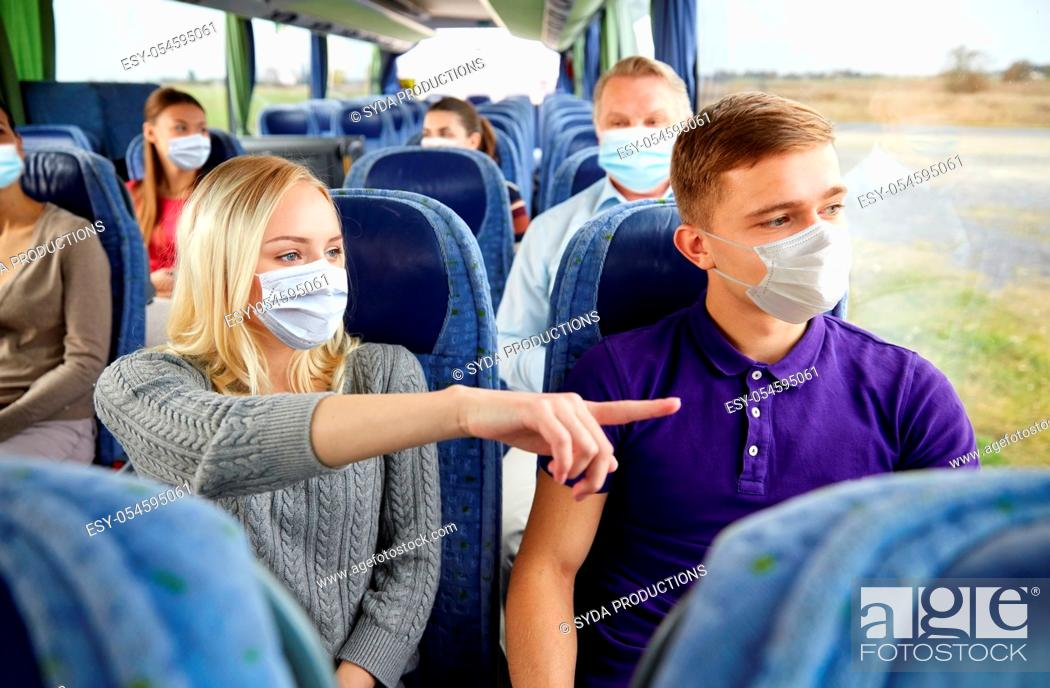 Stock Photo: couple of passengers in masks in travel bus.