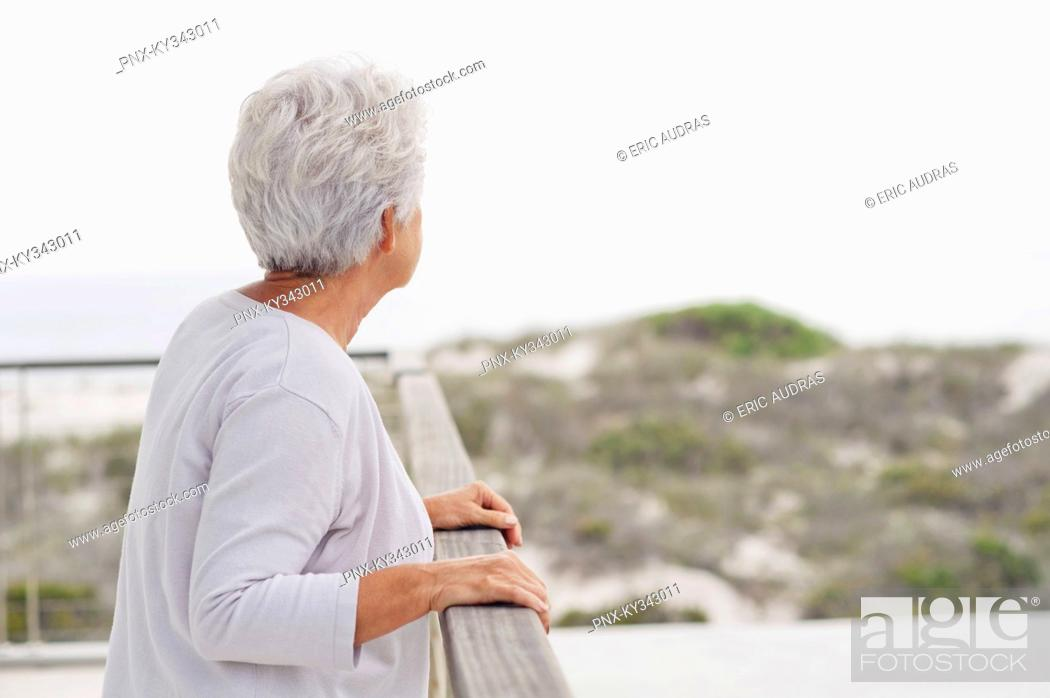 Stock Photo: Senior woman standing at a balcony.