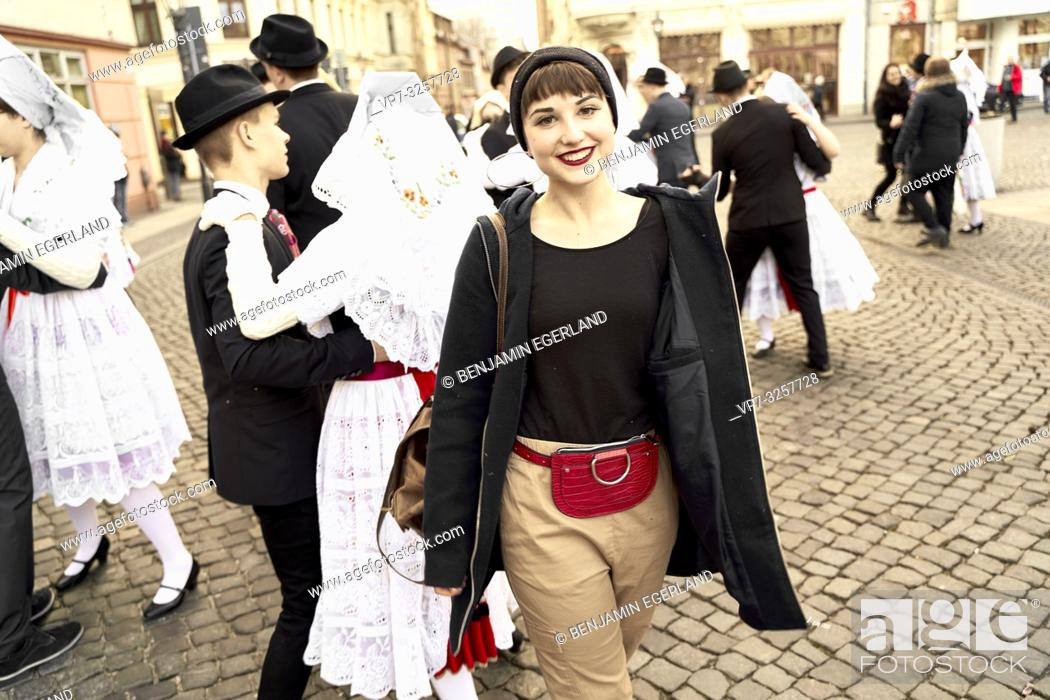 Stock Photo: woman in leisure clothes at German tradition celebration in front of dancing people wearing traditional costume, outdoors at street, in city Cottbus.