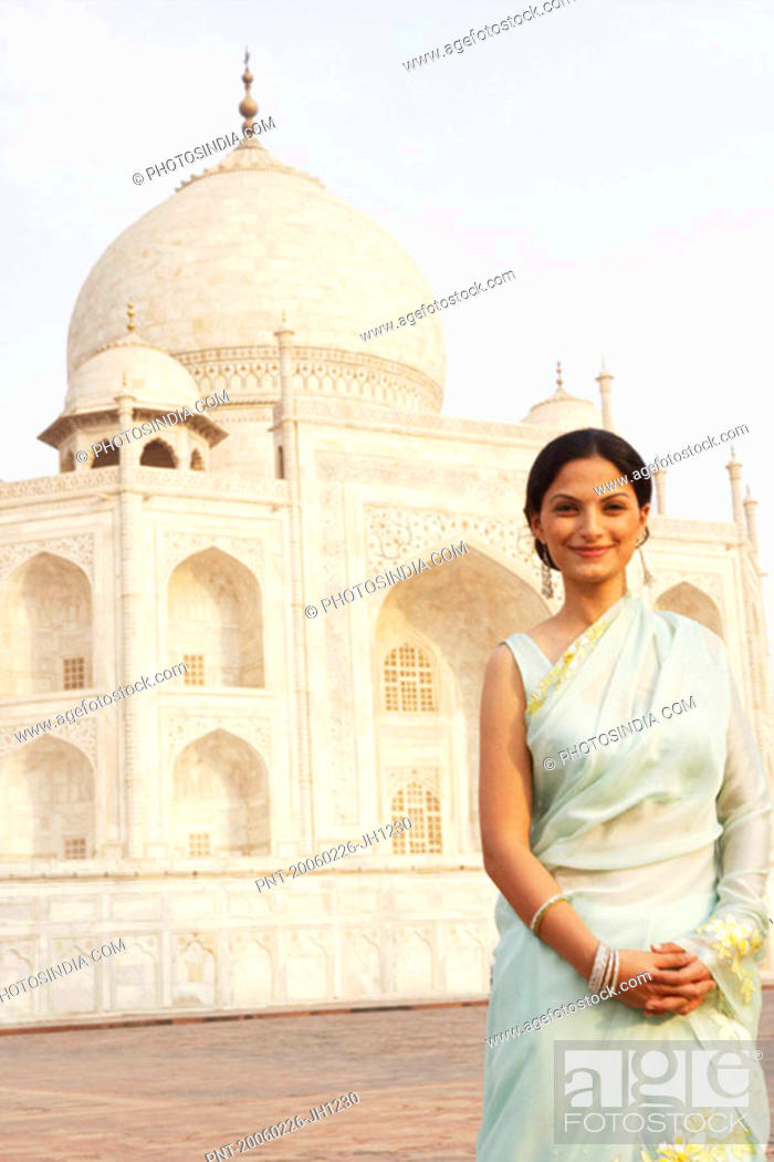 Stock Photo: Portrait of a young woman standing in front of a mausoleum, Taj Mahal, Agra, Uttar Pradesh, India.