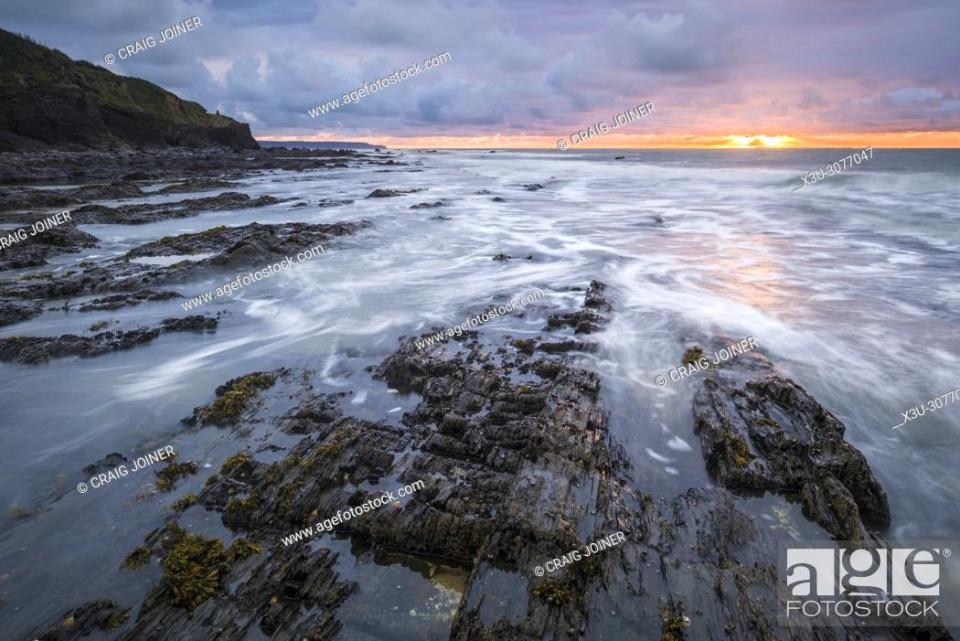 Stock Photo: Sunset over the rocky shore at Westward Ho, North Devon, England.