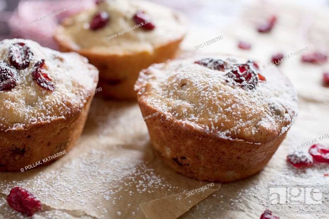 Imagen: Freshly baked cranberry muffins on parchment paper with sugar icing.