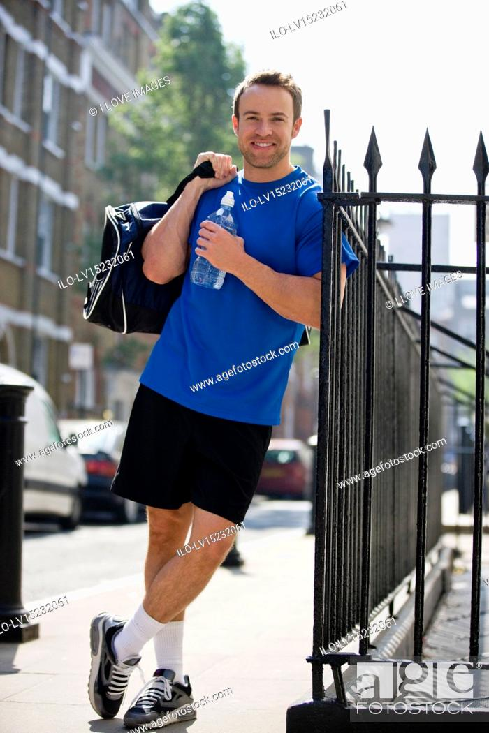 Stock Photo: A young man with a sports bag and bottle of water, leaning against railings.