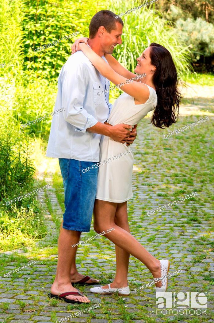Imagen: Joyful couple standing and hugging in park.