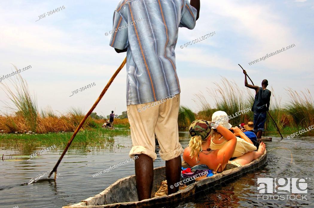 Stock Photo: Tourists on trip in a Mokoro canoe in the Okavango Delta, Botswana.
