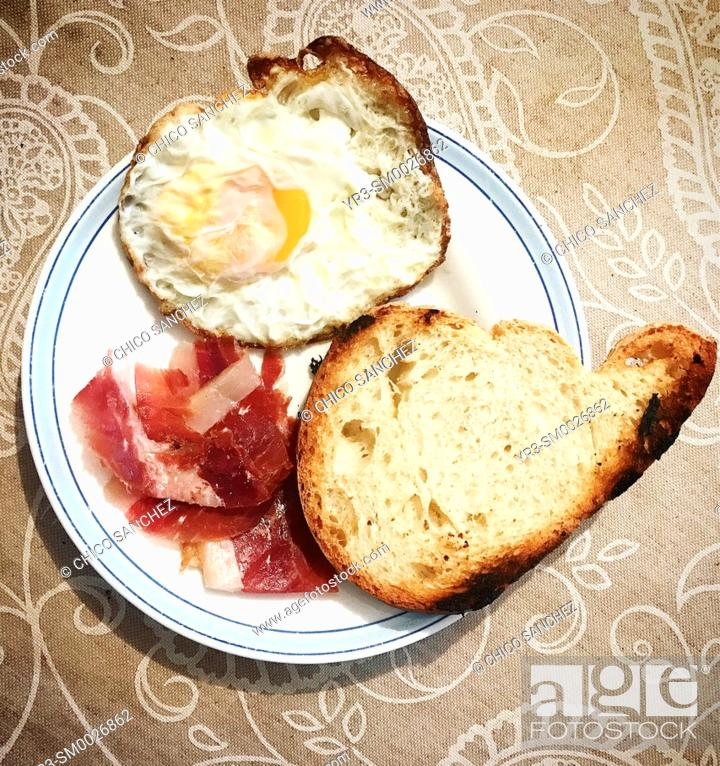 Stock Photo: Toasted bread, Spanish Iberian pig Pata Negra ham and a fried egg for breakfast in Prado del Rey, Sierra de Grazalema, Andalusia, Spain.