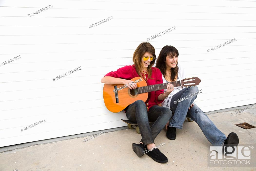 Stock Photo: Two girls sitting on floor with guitar.