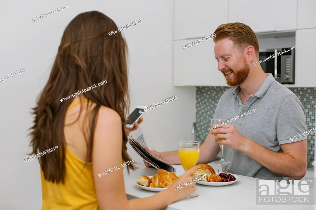Stock Photo: Couple having breakfast in the kitchen.