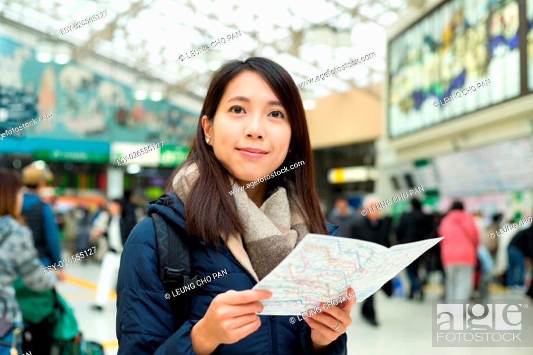 Stock Photo: Woman using map inside train station.