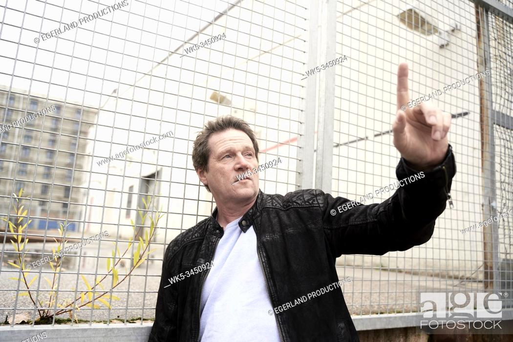 Stock Photo: man with idea in his fifties, pointing at switched off light bulb in industrial area.