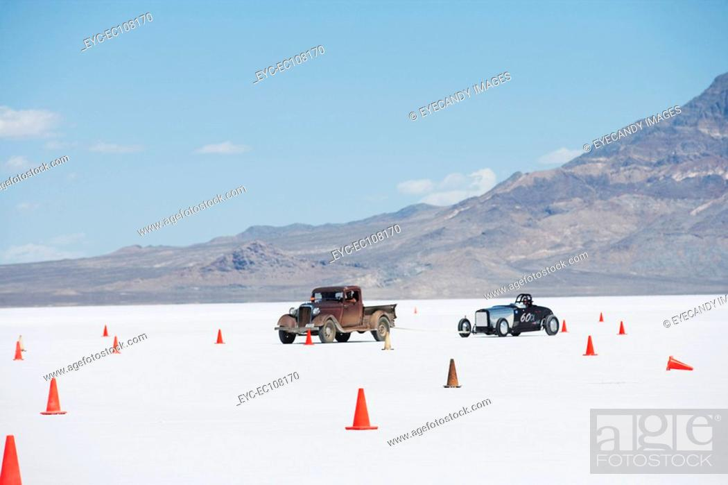 Stock Photo: View of traffic cones on desert by cars against blue sky.
