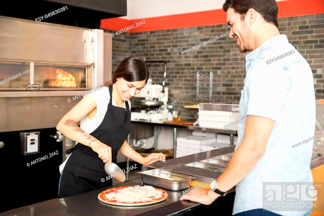 Stock Photo: Smiling customer and chef in a conversation while woman chef preparing pizza in pizza shop.