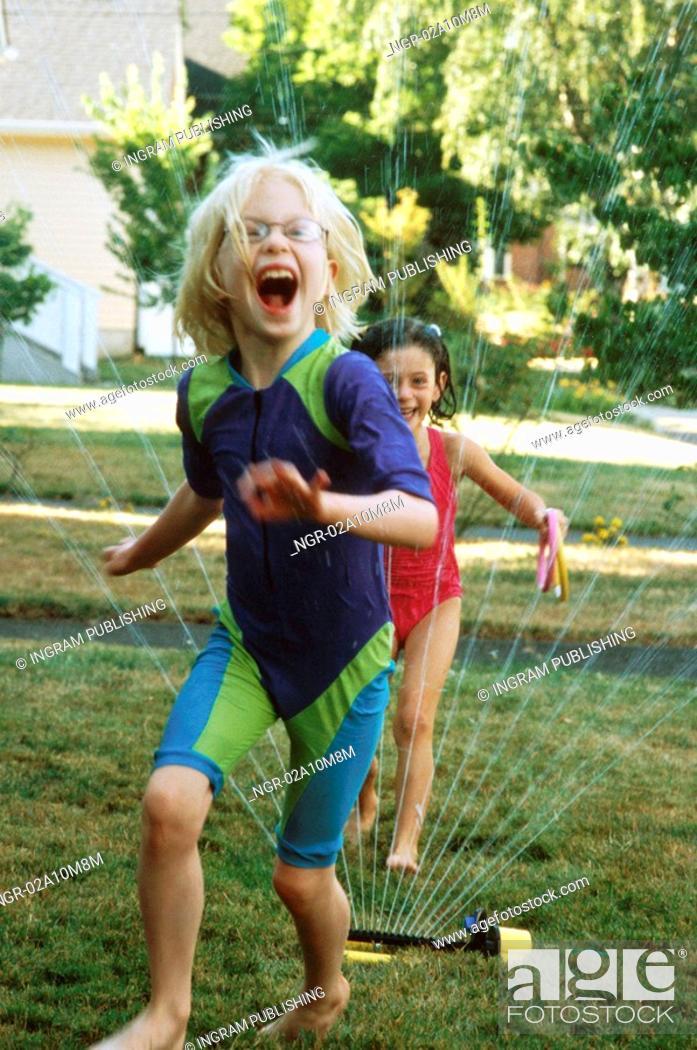 Stock Photo: Girls Laughing and Running Through Sprinkler.