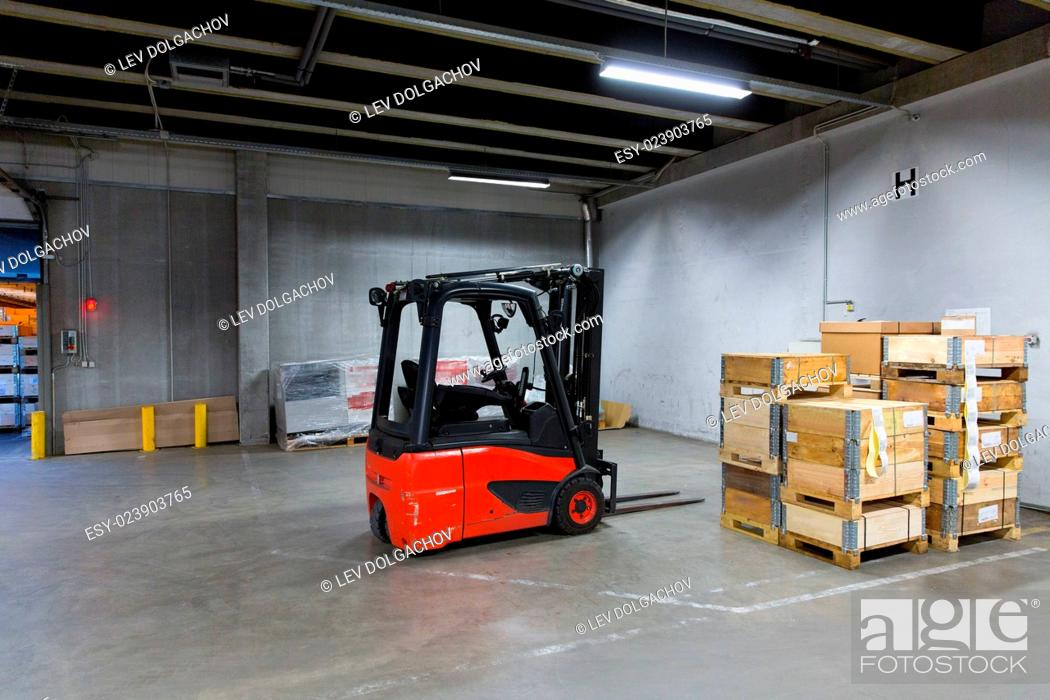 Stock Photo: logistic, storage, loading, shipment and equipment concept - forklift loader and boxes at warehouse.