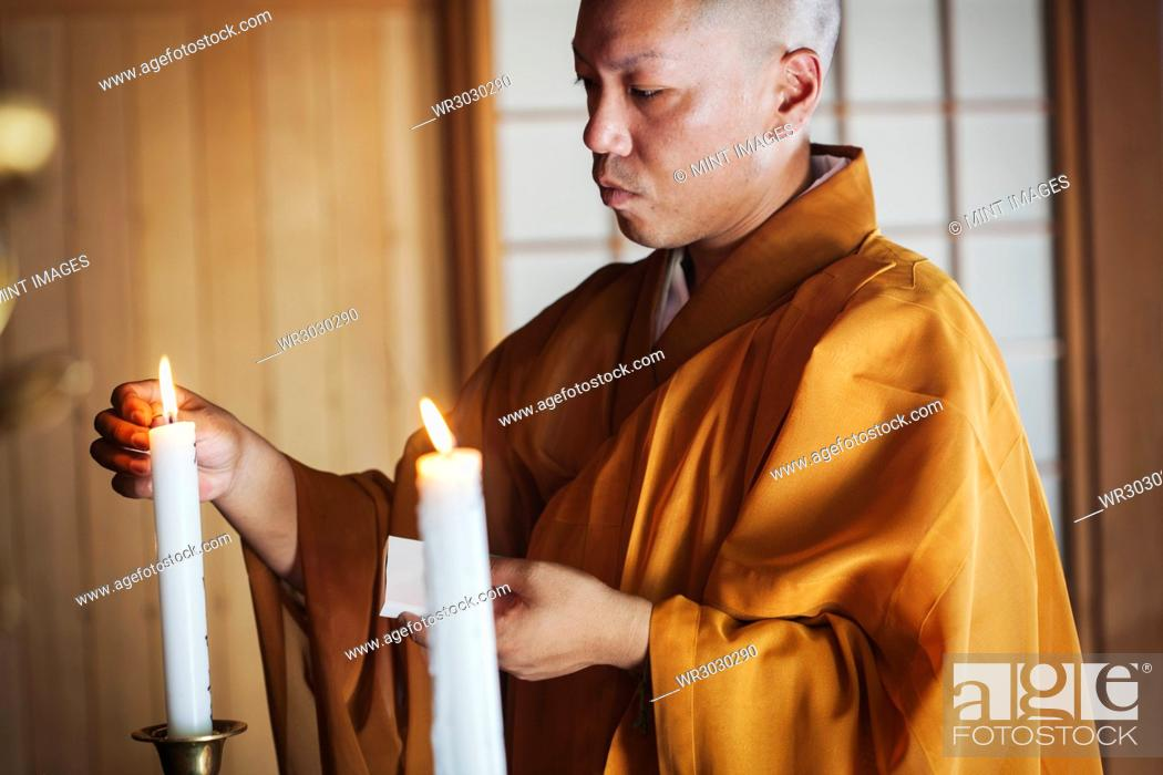 Stock Photo: Side view of Buddhist monk with shaved head wearing golden robe kneeling indoors in a temple, lighting white candle.