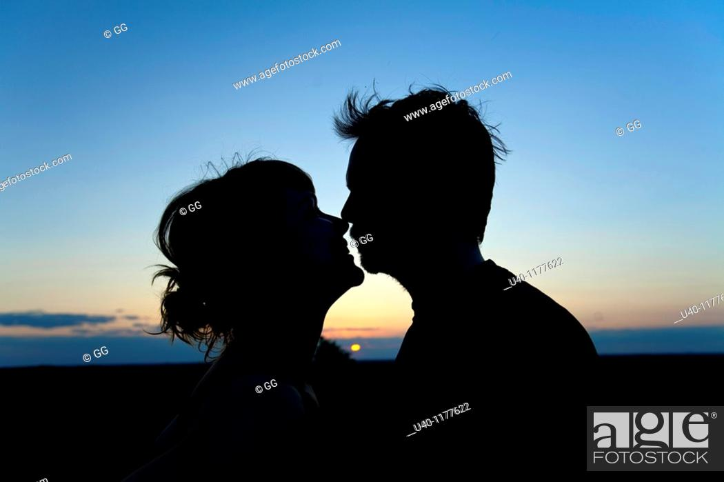 Stock Photo: Couple kissing at sunset.
