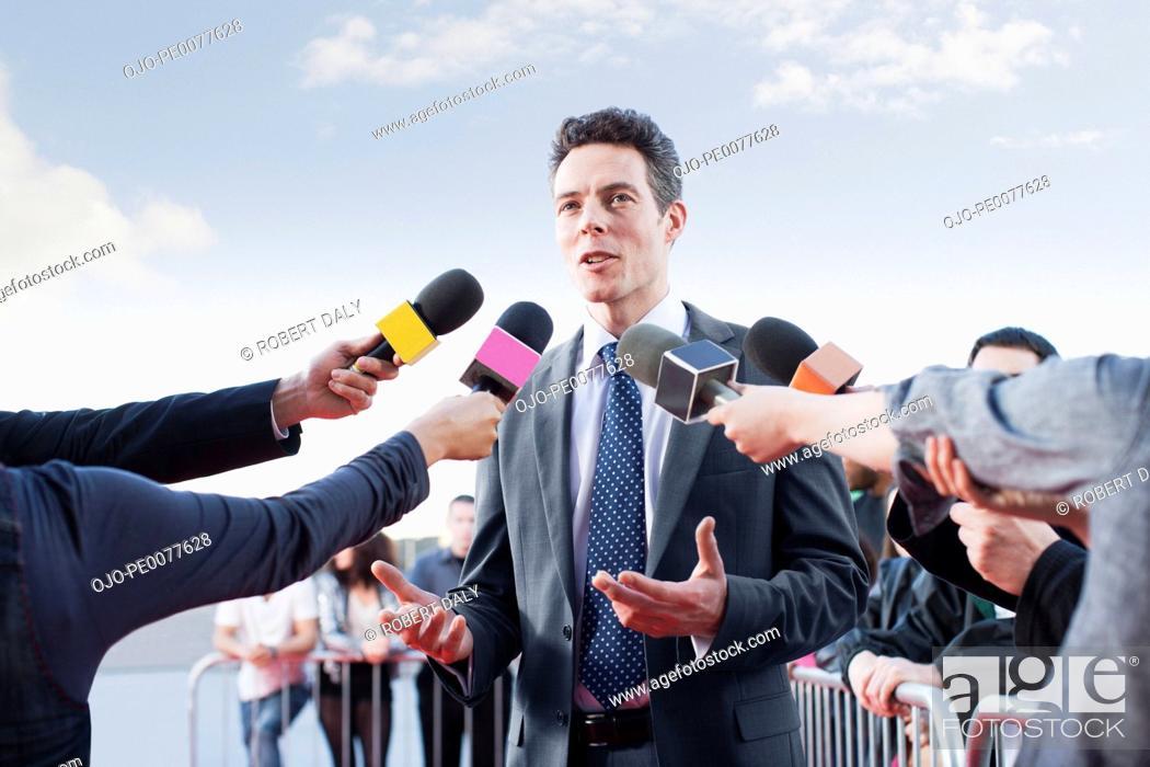 Imagen: Politician talking into reporters' microphones.