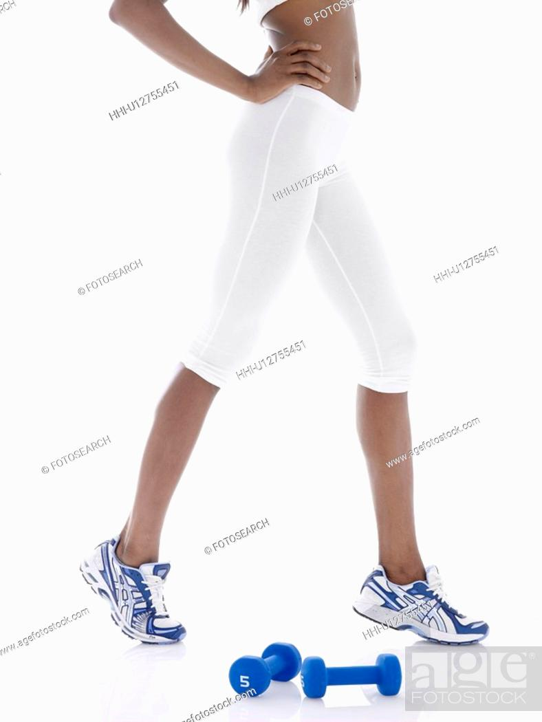 Stock Photo: Young woman with dumbbells stretching (low section).