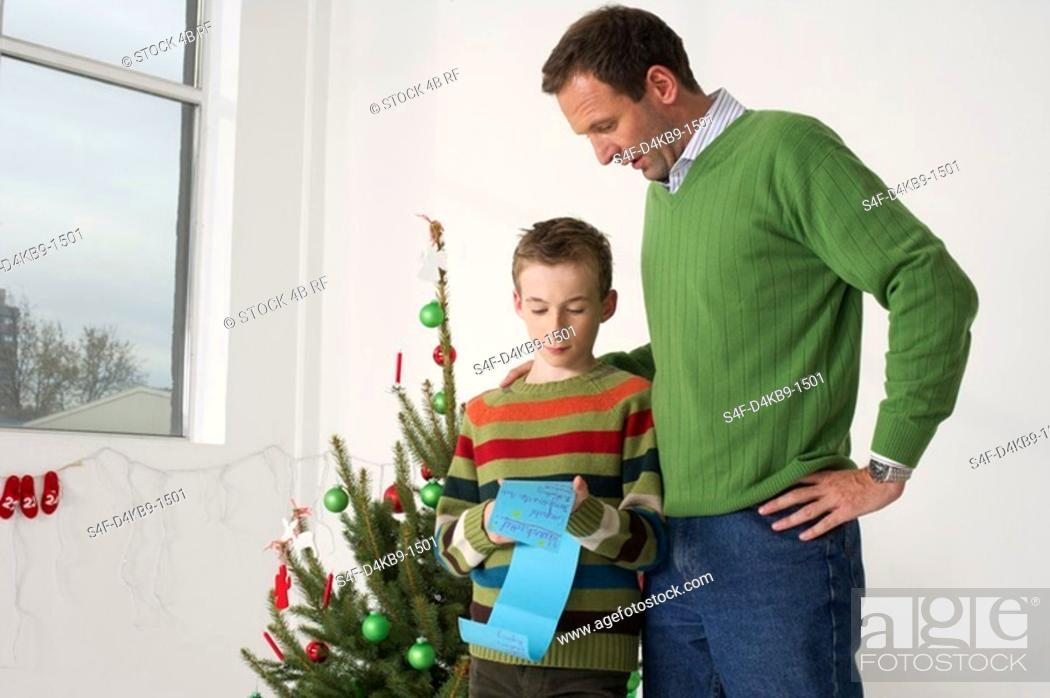 Stock Photo: Boy showing list of wishes to father.