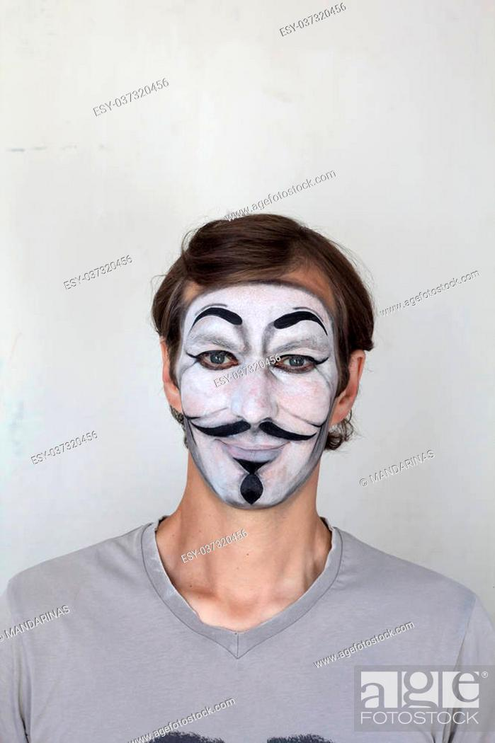 Photo de stock: Smiling man with V mask face painting.