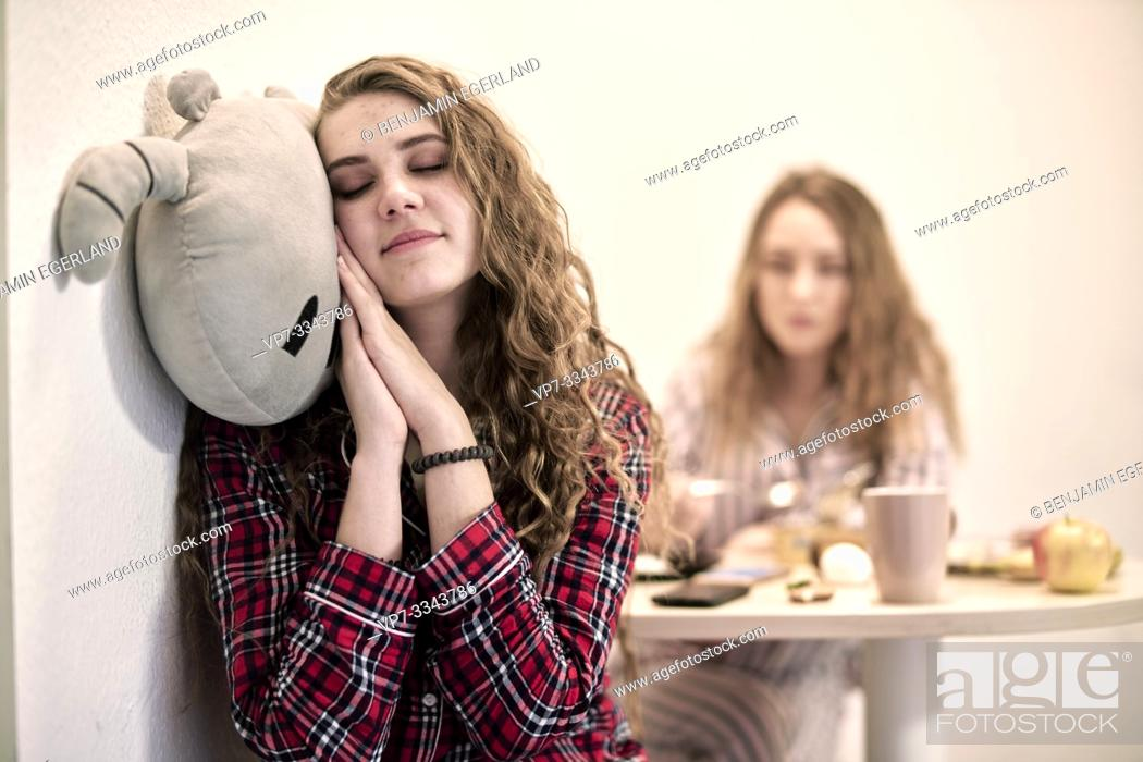 Stock Photo: tired woman cuddling with plushie at breakfast table in morning, starting day in shared student flat.