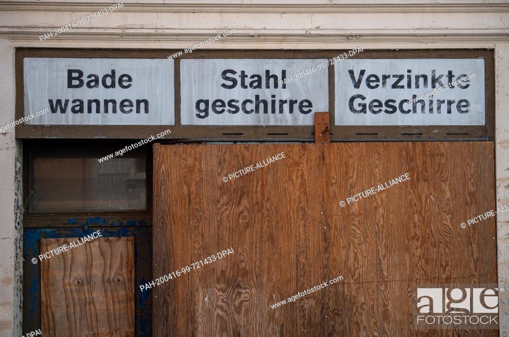 """Stock Photo: 07 April 2020, Saxony, Görlitz: View of a closed shop in Landeskronenstraße with the inscription """"""""Badewannen, Stahlgeschirre und Verzinkte Geschirre""""""""."""
