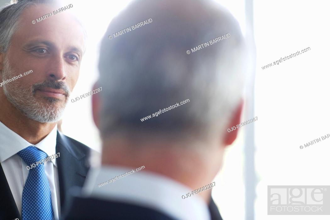 Stock Photo: Close up of businessmen talking at window.