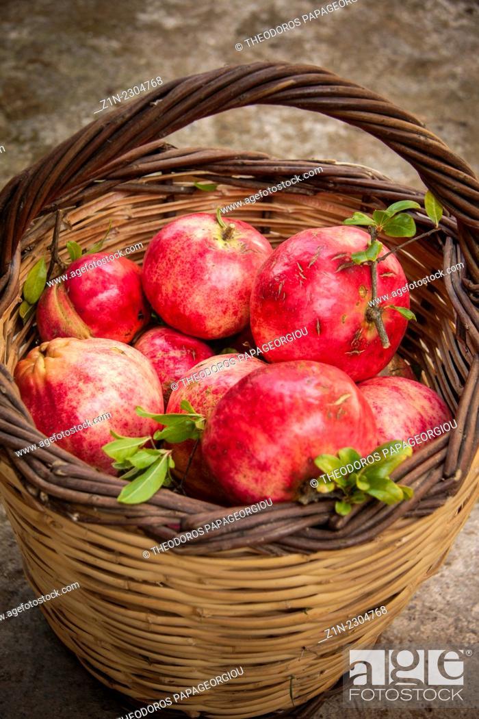 Stock Photo: A basket with pomegranates at Pournaria village. Arcadia, Peloponnese, Greece.